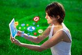 Ung kvinna tittar på moderna tablet med abstrakt lampor och så — Stockfoto