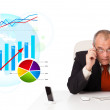 Businessman sitting at desk with statistics - Stock Photo