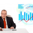 Stock Photo: Businessman sitting at desk with statistics