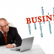 Bisinessman sitting at desk and looking laptop with business wor — Stock Photo