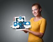 Mladá žena hospodářství tablet s moderní zařízení v mracích — Stock fotografie