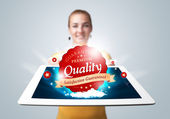 Woman holding tablet with red quality label in clouds — Stock Photo