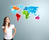 Young woman making phone call with colorful world map — Stock Photo