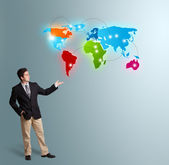 Young man presenting colorful world map — Stock Photo