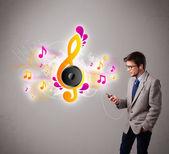 Jeune homme chanter et écouter de la musique avec des notes de musique — Photo