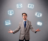 Funny boy juggling with electronic devices icons — Stock Photo