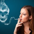 Young woman smoking dangerous cigarette with toxic skull smoke — Stock Photo #16640441