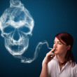 Young woman smoking dangerous cigarette with toxic skull smoke — Stock Photo #16640797