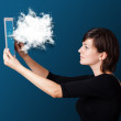 Young woman looking at modern tablet with abstract cloud - ストック写真