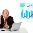 Businessman sitting at desk with laptop and statistics — Stock Photo