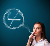 Young lady smoking unhealthy cigarette with no smoking sign — Stock Photo