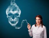 Young woman smoking dangerous cigarette with toxic skull smoke — Stock Photo