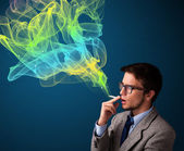 Handsome man smoking cigarette with colorful smoke — Stock Photo