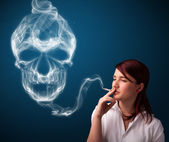 Young woman smoking dangerous cigarette with toxic skull smoke — Stock Photo