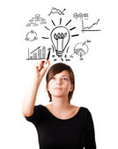 Young business woman drawing light bulb with various diagrams an — Stock Photo