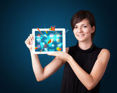 Woman holding modern tablet with colorful diagrams and graphs — 图库照片