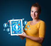 ソーシャル ネットワークのアイコンを持つ若い女性持株タブレット — ストック写真