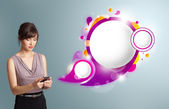 Pretty woman holding a phone and presenting abstract speech bubb — Stock Photo