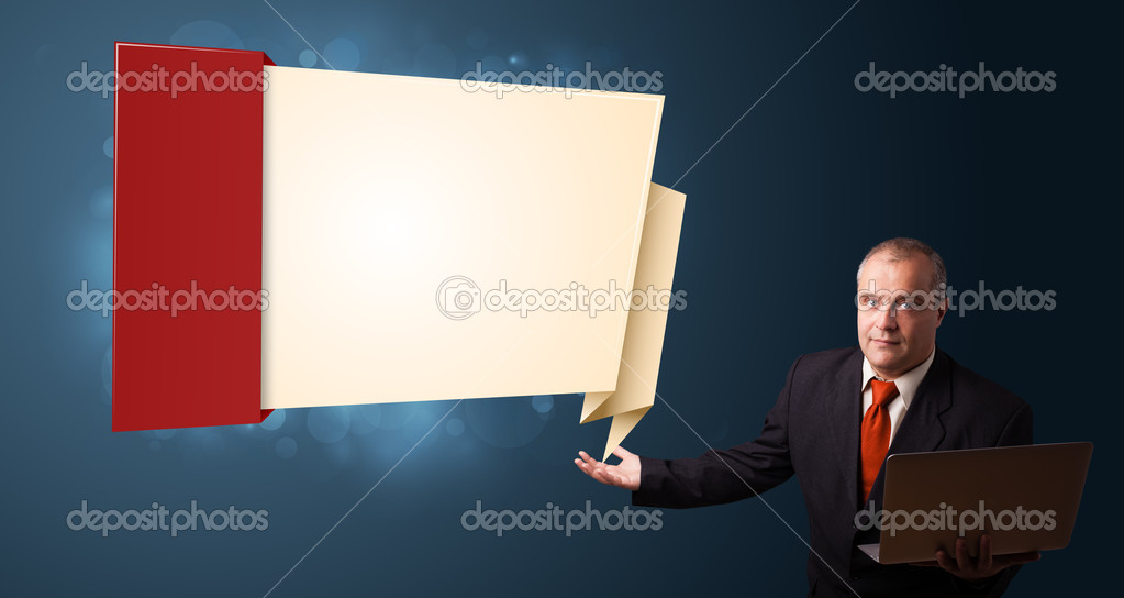 Businessman in suit holding a laptop and presenting modern origami copy space — Stock Photo #16642459