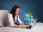 Beautiful girl sitting at desk and watching her photo gallery on — Stok fotoğraf