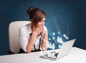 Mujer sentada en el escritorio y escribiendo en portátil con diagramas — Foto de Stock