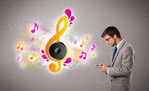 Young man singing and listening to music with musical notes — Stock Photo
