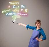 Joven mujer cocina vitaminas y minerales — Foto de Stock