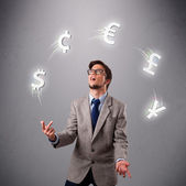 Young man standing and juggling with currency icons — Stock Photo