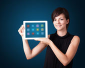 Woman holding modern tablet with colorful icons — Stock Photo