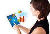 Jonge vrouw op zoek naar moderne tablet met kleurrijke diagrammen — Stockfoto
