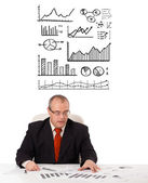 Businessman sitting at desk with statistics and graphs — ストック写真