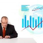 Постер, плакат: Businessman sitting at desk with statistics