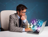 Handsome man sitting at desk and typing on laptop with 3d number — Stock Photo