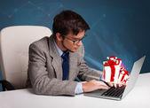 Homem bonito sentado na mesa e digitar no laptop com presente b — Foto Stock