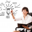 Young business woman drawing light bulb with various diagrams an — Stock Photo #19462411