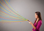 Happy girl holding a phone with colorful abstract lines — Stok fotoğraf