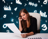 Young businesswoman sitting at desk with diagrams and statistics — Foto de Stock
