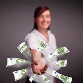 Mooie vrouw permanent en gooien geld — Stockfoto