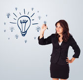 Woman drawing light bulb on whiteboard — Stock Photo