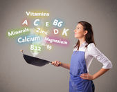 Young woman cooking vitamins and minerals — Stock Photo