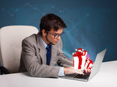 Handsome man sitting at desk and typing on laptop with present b — Stock Photo