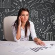 Businesswomsitting at desk with business scheme and icons — Stock Photo #20801615