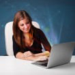 Beautiful woman sitting at desk and typing on laptop with abstra — Stock Photo #21346521