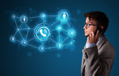 Young boy making phone call with social network icons — Stock Photo
