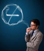 Young man smoking unhealthy cigarette with no smoking sign — Stock Photo