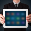 Businessman holding a white modern tablet with blurry apps — Stock Photo