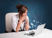 Young lady sitting at dest and typing on laptop with message ico — Stok fotoğraf