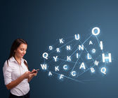Young woman typing on smartphone with high tech 3d letters commi — Stock Photo