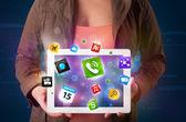 Dama segurando um tablet com apps coloridos modernos e ícones — Foto Stock