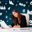 Young businesswoman sitting at desk with diagrams and statistics — Stock Photo #22568395